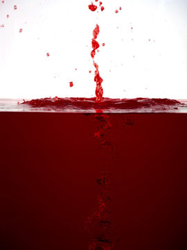 Red colour liquid dripping into water