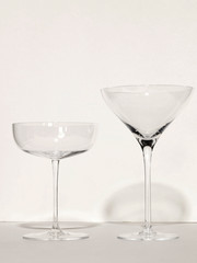 Two empty cocktail glasses, white background
