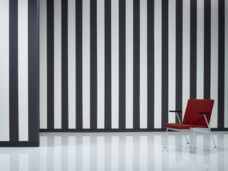 Red armchair by black and white striped wall
