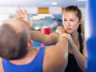 Girl and her trainer are practicing punches in gym