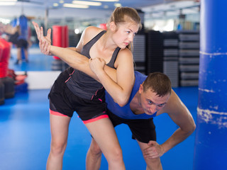 Woman training on the self-defense course with trainer