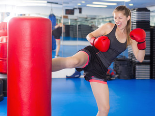 Active woman practicing with punching bag in box gym