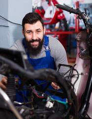 Worker repairing motorbike