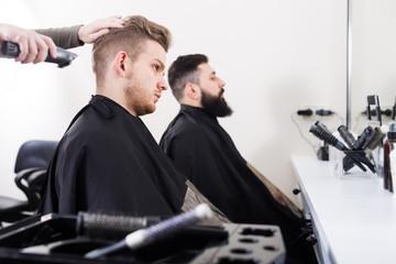 Adult men having their hair cut by hairdressers