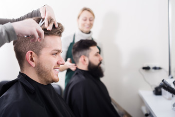 Clients having their hair cut by hairdressers
