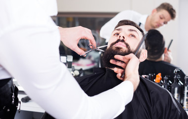Smiling guy creating shape for beard of client