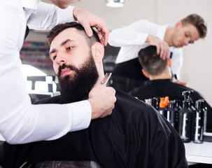 Adult stylist creating shape for beard of client