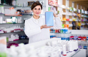 Professional female pharmacist is showing right drug