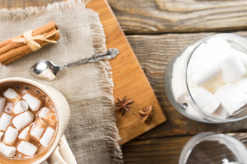 Hot Chocolate, Marshmallow and cinnamon on rustic table