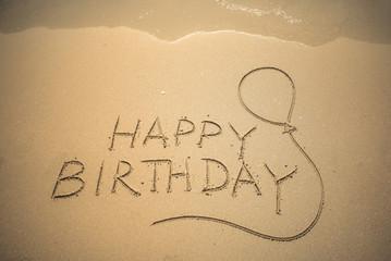 Happy Birthday word is written on the beach sand