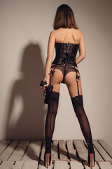 sexy young woman in a leather black corset, lacy panties and stockings