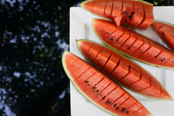 Top view flat lay sliced red watermelon on plate on black glass table with trees in reflection. Summer food, refreshment, vegetarian food, detox. Text space