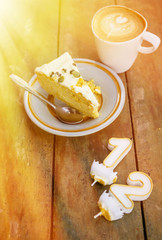 Slice of birthday cake witn candle numbers one and two with cup of latte on wooden table in warm sun light. Text space