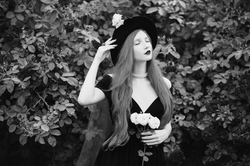 Redhead woman with very long hair with unusual appearance in black dress against background of red roses. Attractive girl with pale skin and bright appearance with black hat and red veil. Art photo