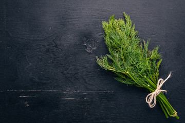Fresh green dill on a wooden background. Top view. Free space for your text.