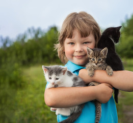 kitten on arm of the boy outdoors, child huge his love pet