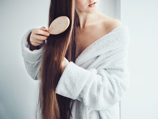 Cute, young woman in a soft, terry dressing gown, combing her hair after Spa Services and Spa Treatments