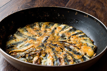 Fresh Fried Sardines in Pan on Wooden Surface.