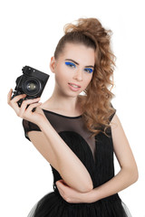 Young beautiful girl with makeup and haircut with a camera in her hand isolated on white background. Studio photography.