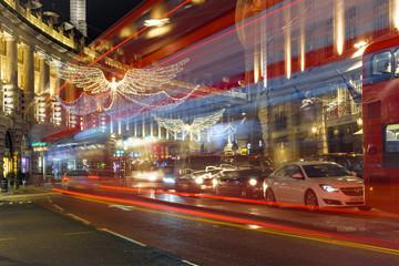london sliberty street at night with london bus trail traffic jam christmas angels light