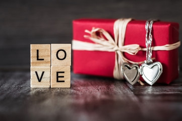 gift in red box, a pendant in the shape of a heart on a silver chain and the word love, lined with square wooden blocks, on dark wooden background