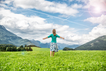 Young woman staying on the green field