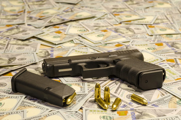 The weapon with blurred bullets laid down on blurred dollars