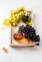 Photo on top of wooden tray with green and black grapes, two bottles of juice