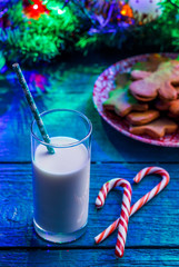 Picture of Christmas cookies, glass of milk, caramel sticks, spruce branches with burning garland