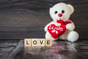 soft toy white bear holding a heart and the word love, lined with wood blocks, on dark wooden background