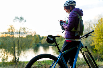 Picture of woman in helmet standing with phone in hands near bicycle