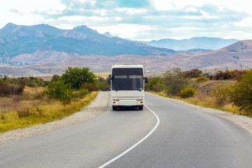 Bus is moving on a country road in a mountainous area