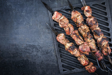 Poster Grill / Barbecue Traditional Russian shashlik on a barbecue skewer as top view on grillage with copy space left
