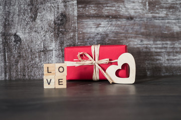 gift in red box, the wooden heart and the word love, lined with square wooden blocks, on dark wooden background
