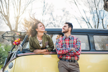 Woman and man enjoy in classic van.