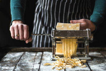 Female preparing homemade tagliatelle with machine on the table,selective focus