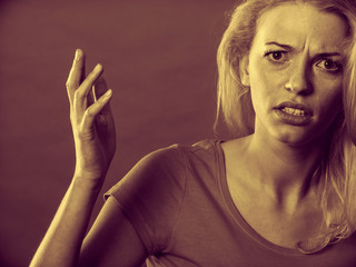 Angry, shocked blonde woman gesturing hands