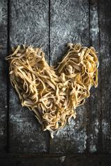 Prepared Italian traditional tagliatelle in heart shape on wooden background,Valentine day concept