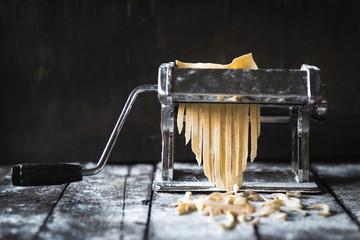 Italian traditional tagliatelle in machine for preparing,selective focus