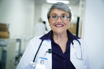 Portrait of smiling female doctor standing in hospital