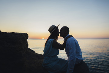 Young couple kissing on rock near ocean at sunset