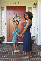 Smiling mixed race mother and daughter standing on front stoop