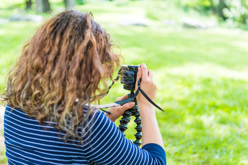 Back of young woman taking pictures in green outdoor park with camera and tripod in summer