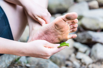 Closeup of young woman's dirty foot with her cleaning dirt with green leaf in nature by rocks