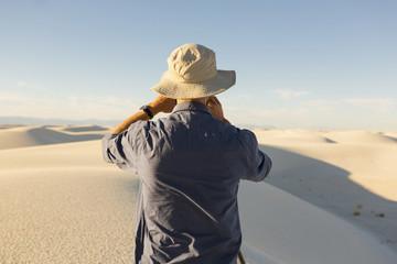 Caucasian man photographing a desert landscape