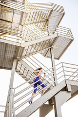 Caucasian woman running on urban staircase
