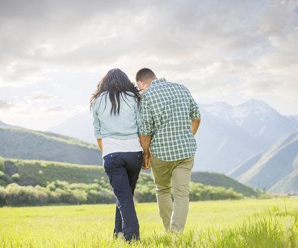 Couple holding hands walking near mountain