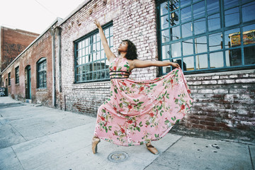 Mixed race ballet dancer wearing dress on sidewalk