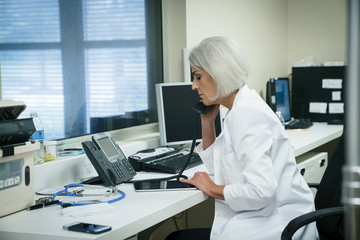Caucasian doctor talking on telephone and using digital tablet