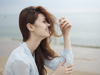 Smiling woman holding hair sitting on beach